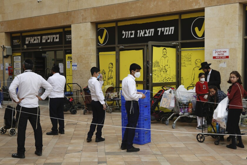 Ultra-Orthodox Jews wait to enter a supermarket while keeping a safe social distance as part of the Israeli government's measures to stop the coronavirus.