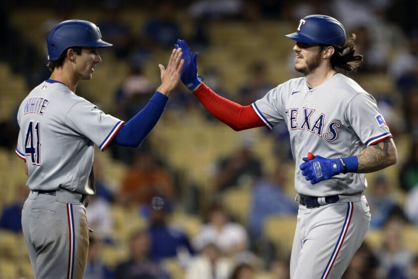 Texas Rangers' Jonah Heim, right, gets congratulations from Eli White after hitting a two-run home run against the Los Angeles Dodgers during the fourth inning of a baseball game in Los Angeles, Saturday, June 12, 2021. (AP Photo/Alex Gallardo)