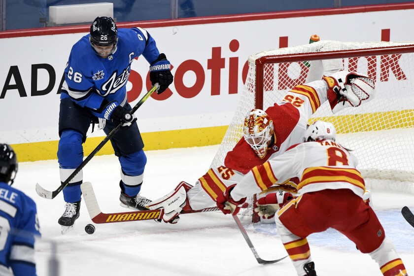 Calgary Flames goaltender Jacob Markstrom (25) makes a save against Winnipeg Jets' Blake Wheeler (26) during first-period NHL hockey game action in Winnipeg, Manitoba, Monday, Feb. 1, 2021. (Fred Greenslade/The Canadian Press via AP)