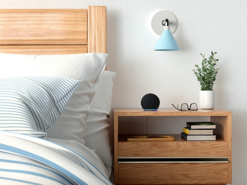 An Amazon Echo Dot sits on a bedside table.