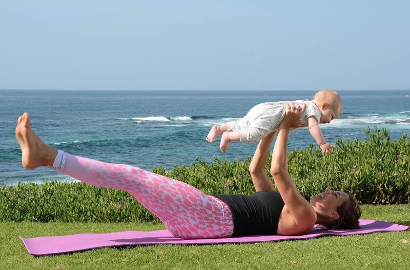 Magdalena Patterson does yoga-based exercises with her daughter Alessandra at Scripps Park.