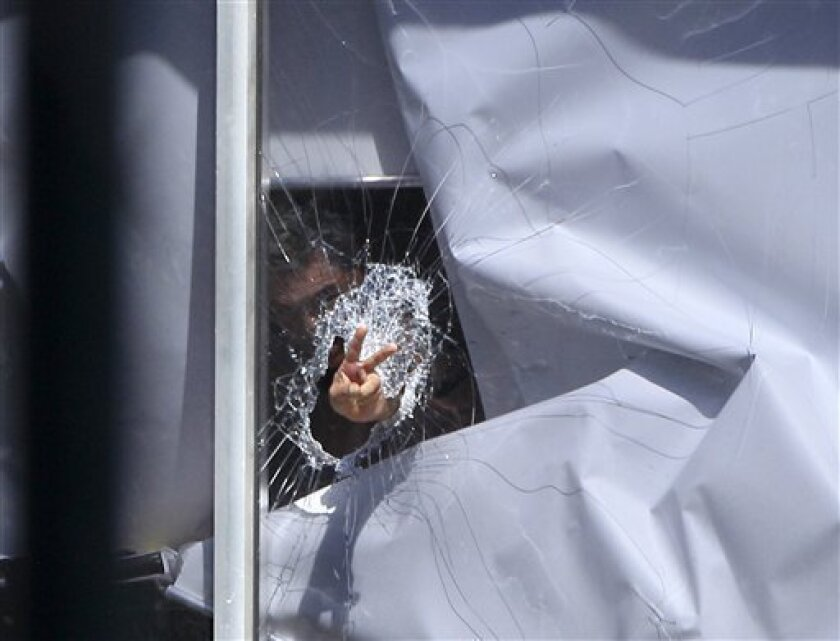 A man believed to be holding a child hostage gestures after smashing a window at a lawyers office in suburban Sydney, Tuesday, Sept. 6, 2011. Australian police cordoned off a Sydney building Tuesday in a tense standoff with the man who claimed to have a bomb, smashed a window and issued threats from the lawyer's office where he holed up with his teenage daughter. (AP Photo/Rick Rycroft)