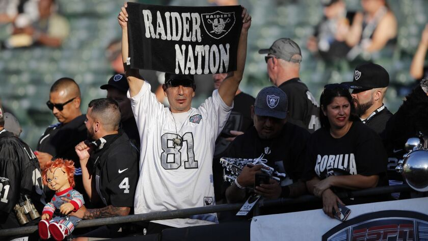 An Oakland Raiders fan watches warmups before the start of an NFL football game against the Los Ange