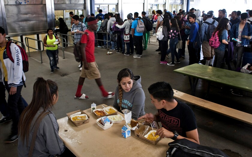 Mele Vehikite, 16, left, Ellie Gutierrez, 17, and Antonio Ramos, 18, eat lunch at Washington Preparatory High School in L.A. The school is required to serve three items, including a fruit and a vegetable, even if students do not want them.