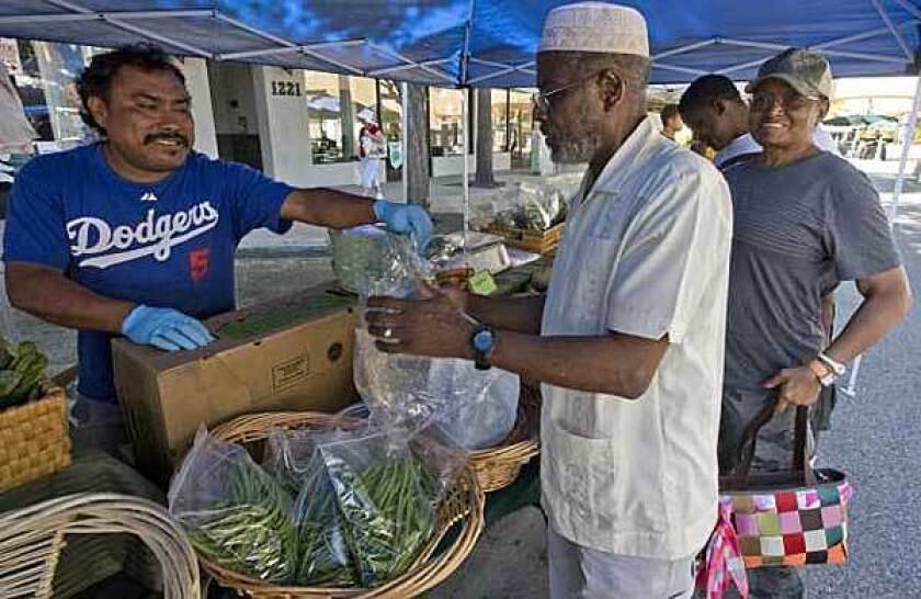 Santiago Morelos sells greens and vegetables grown in Santa Paula by Abundio Ruiz of Gourmet Specialties, at the Torrance downtown farmers market.