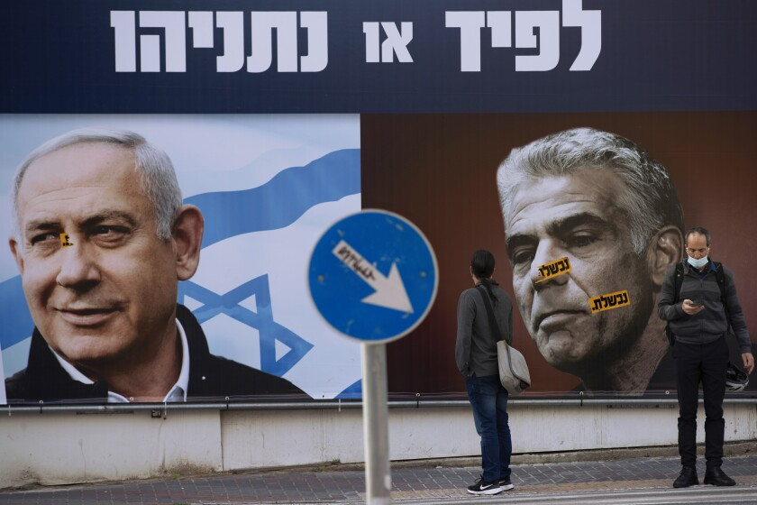 In this Sunday, March. 14, 2021 file photo, people stand in front of an election campaign billboard for the Likud party showing a portrait of its leader Prime Minister Benjamin Netanyahu, left, and opposition party leader Yair Lapid, in Ramat Gan, Israel. Israel's President Reuven Rivlin has tapped opposition leader Yair Lapid to form a new government, a step that could lead to the end of the lengthy rule of Prime Minister Benjamin Netanyahu. Rivlin announced his decision on live television a day after Netanyahu failed to cobble together a governing coalition by a midnight deadline. (AP Photo/Oded Balilty, File)