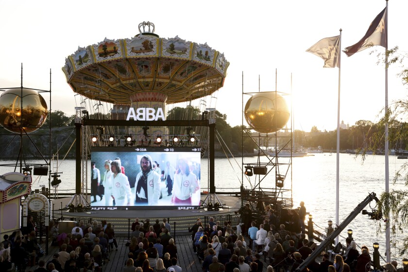 At water's edge, a small audience watches a big screen showing the group ABBA.