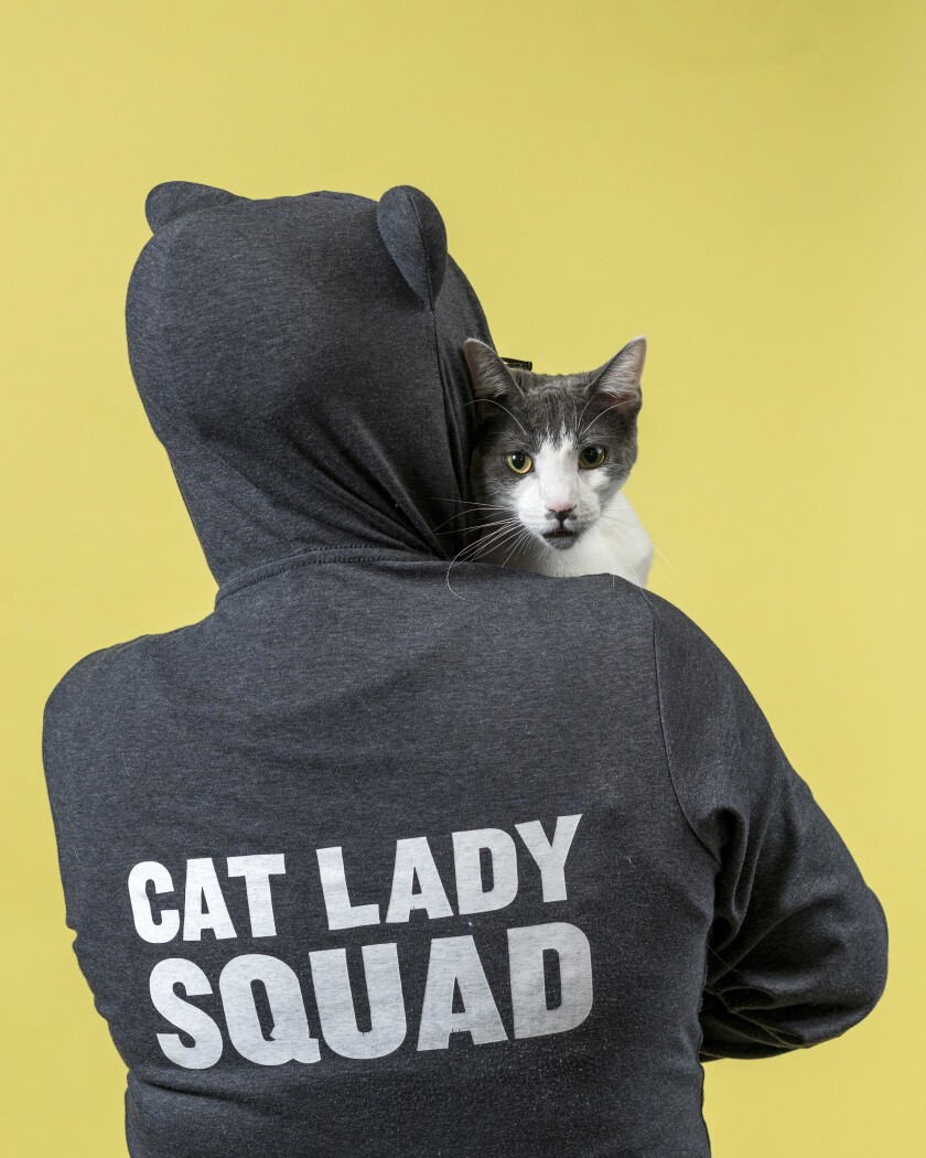 """Stoffel the cat looks over the shoulder of Esther Su, who is wearing a hoodie that says """"Cat Lady Squad."""""""