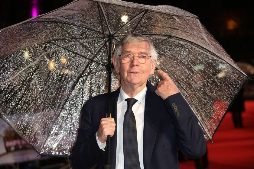 Actor Tom Courtenay stands in the rain under a clear umbrella