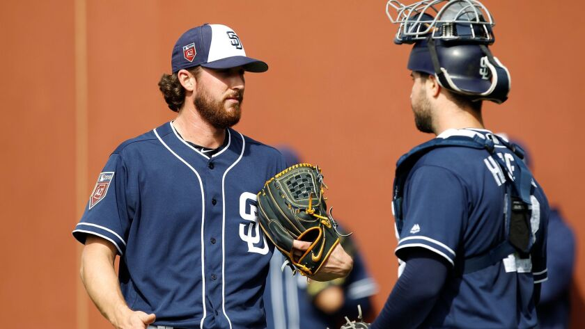 New Padres pitcher Bryan Mitchell, here talking with catcher Austin Hedges during a spring training workout, will start for the Padres on Sunday against the Angels.