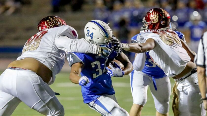 Rancho Bernardo running back Tahj Martin gets face masked by Mission Hills' Shiloh Seau (99) and Rob