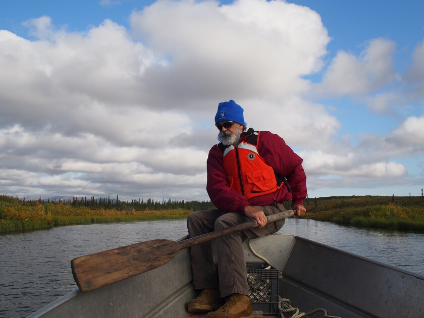 Jay Denton rows a boat along a creek off the Noatak River.
