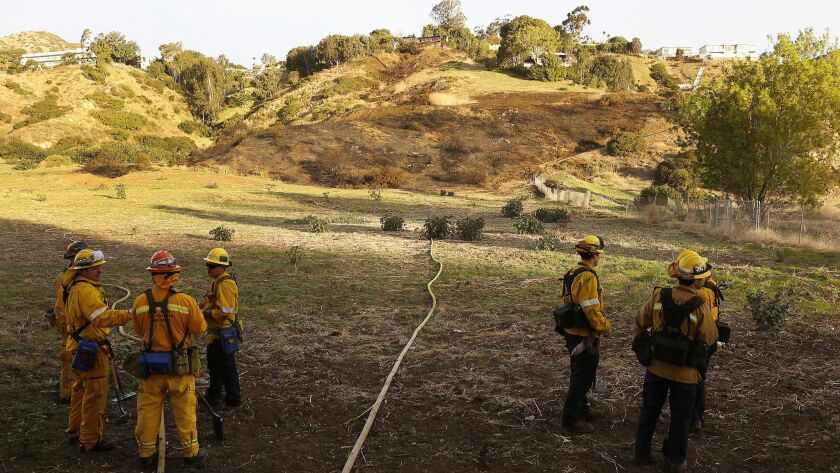 Los Angeles County firefighters prepare to put out hot spots on a scorched hillside where they fought a 2.6-acre brush fire behind the Malibu Library.