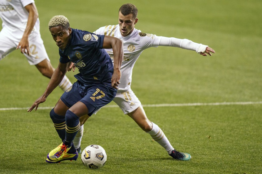 Philadelphia Union's Sergio Santos, left, battles with Atlanta United's Brooks Lennon, right, for the ball during the first half of a CONCACAF Champions League soccer match, Tuesday, May 4, 2021, in Chester, Pa. (AP Photo/Chris Szagola)