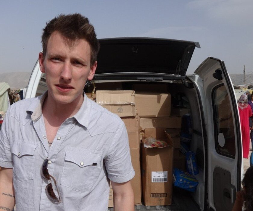 This undated photo provided by Kassig Family shows Peter Kassig standing in front of a truck filled with supplies for Syrian refugees. A video purportedly produced by militants in Syria released Friday, Oct. 3, 2014, shows Kassig, of Indianapolis, kneeling on the ground as a masked militant says he will be killed next. (AP Photo/Courtesy Kassig Family)