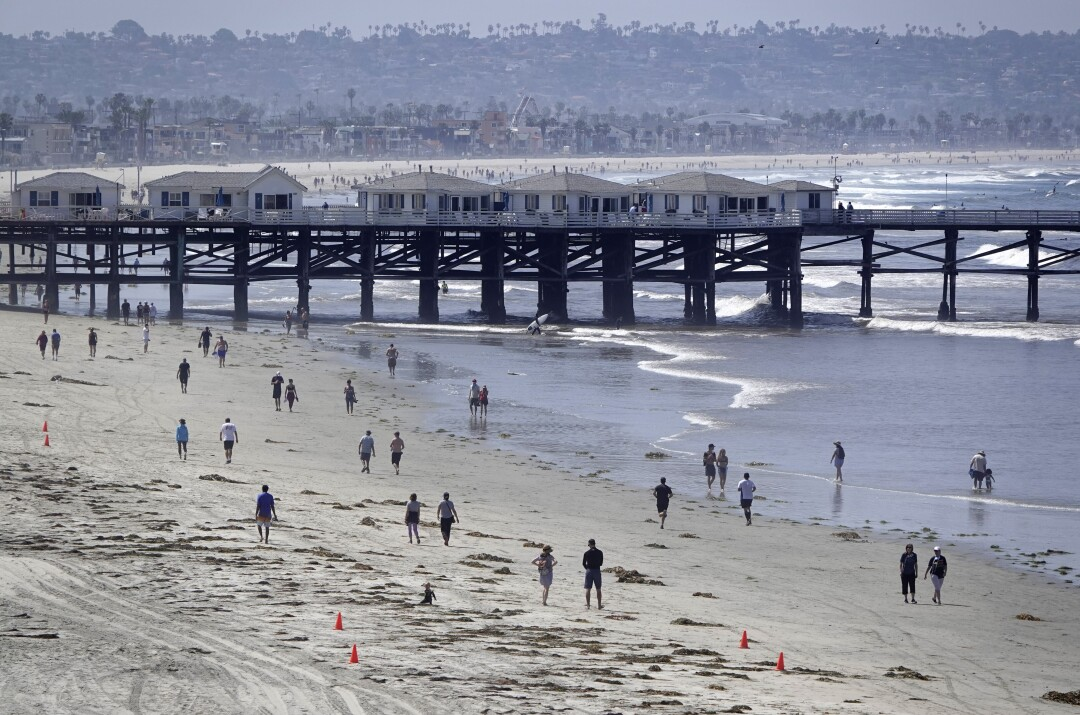 People walk along the coast in Pacific Beach after local beaches reopened to activities such as walking, running, and surfing on April 27, 2020. Beaches have been closed for several weeks due to the coronavirus. The boardwalks and congregating on the sand are still prohibited.