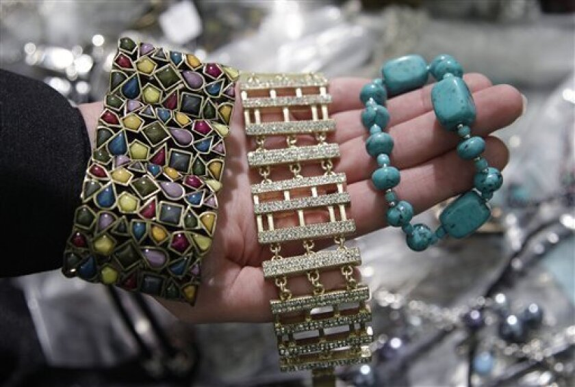 FILE - In this Dec. 13, 2011, file photo, a California Department of Justice employee holds up counterfeit jewelry that was confiscated during an investigation before it was sold on eBay during a news conference in San Jose, Calif. If a purse with $900 is stolen, the victim probably would call the