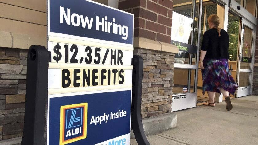 "FILE- In this July 17, 2018, file photo, a sign outside a business in Salem, N.H. says ""Now Hiring."""