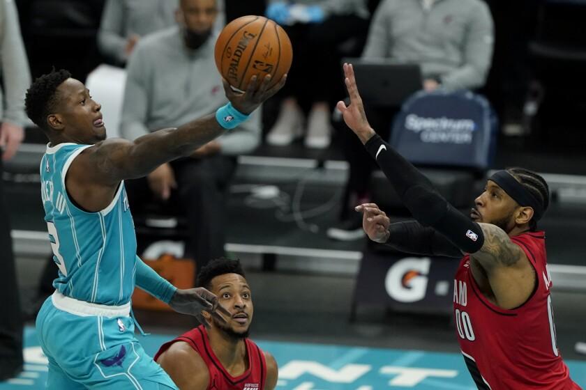 El base de los Hornets de Charlotte Terry Rozier dispara ante la defensiva del alero de los Trail Blazers de Portland Carmelo Anthony en la segunda mitad del juego del domingo 18 de abril de 2021, en Charlotte, Carolina del Norte. (AP Foto/Chris Carlson)