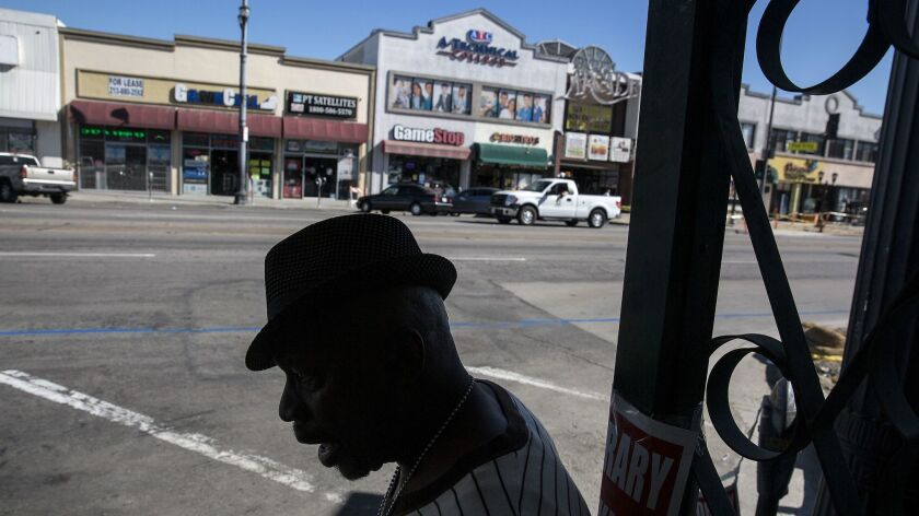 Carl Green, 59, of Lynwood, waits for a bus at Pacific and Clarendon avenues in Huntington Park.
