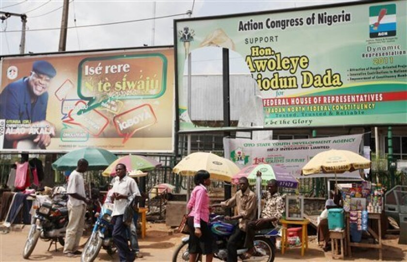People walk past a torn Campaign billboard of an opposition Party, right, and the ruling party left, in Ibadan, Nigeria, Friday, April 1, 2011. The first of three crucial elections in Nigeria will be held Saturday and as elsewhere in the country, politics often comes down to personality over policy. In the city of Ibadan, once the shining jewel of the postcolonial era in Africa, fighting within the ruling People's Democratic Party has seen deaths and riots over recent weeks. That comes atop efforts by an opposition party to take Ibadan and the rest of Oyo state in Nigeria's southwest. (AP Photo/Sunday Alamba)