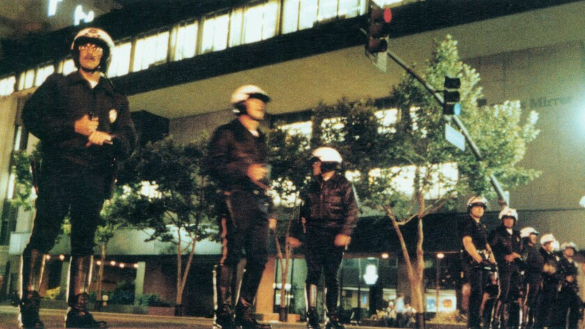 Los Angeles Police officers form a line across 1st Street in front of the Los Angeles Times building after rioters smashed windows on April 29, 1992.