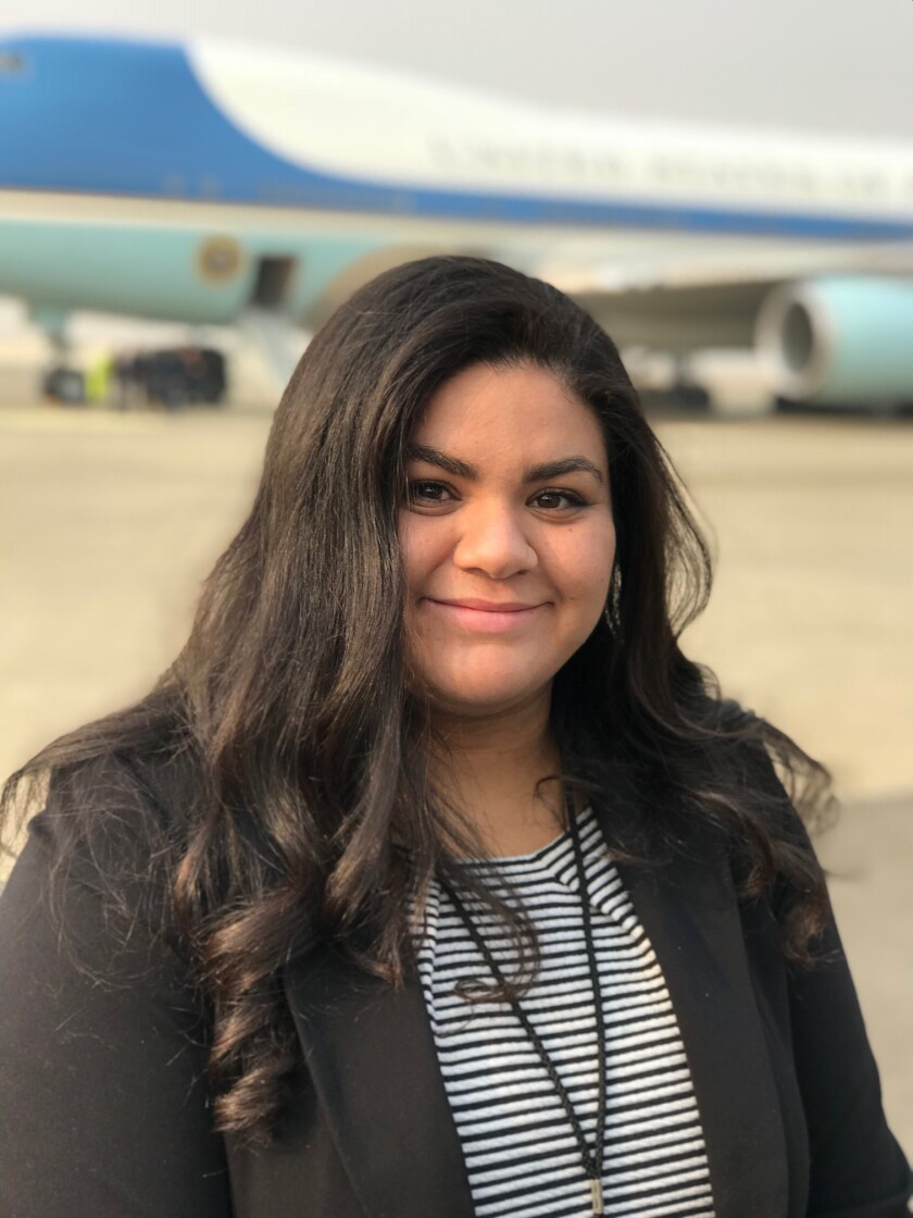 Chico Enterprise-Record reporter Bianca Quilantan, 23, shown here with Air Force I in the background, covered President Donald Trump's visit to California after the Camp Fire swept through Paradise and neighboring towns beginning Nov. 8, 2018. She contributed to the newspaper's ongoing coverage of the devastating wildfire and its aftermath, a package which became a 2019 Pulitzer Prize finalist.