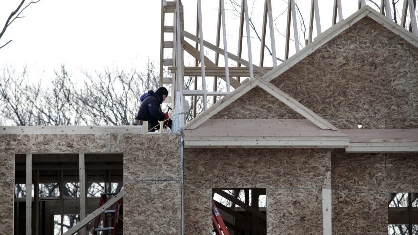 In this Jan. 23, 2019, photo, construction workers build new housing in Salisbury, Mass. On Friday,