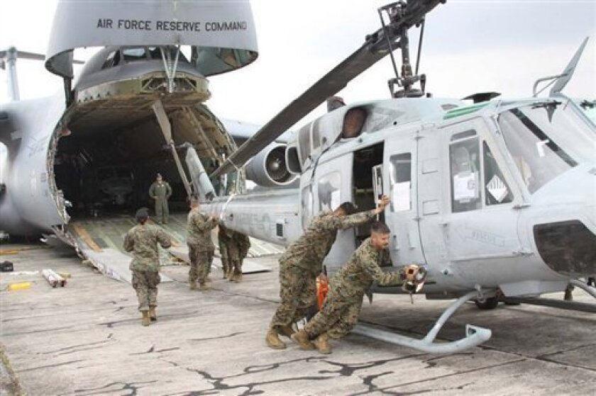 In this image released by the U.S. Marine Corps on Wednesday Aug. 29, 2012,  Marines from Marine Light Attack Helicopter Squadron 467 (HMLA-467) unload a UH-1N Huey helicopter in Guatemala City, Aug. 11, 2012.  A team of 200 U.S. Marines and four UH-1N Huey helicopters has begun patrolling Guatemal