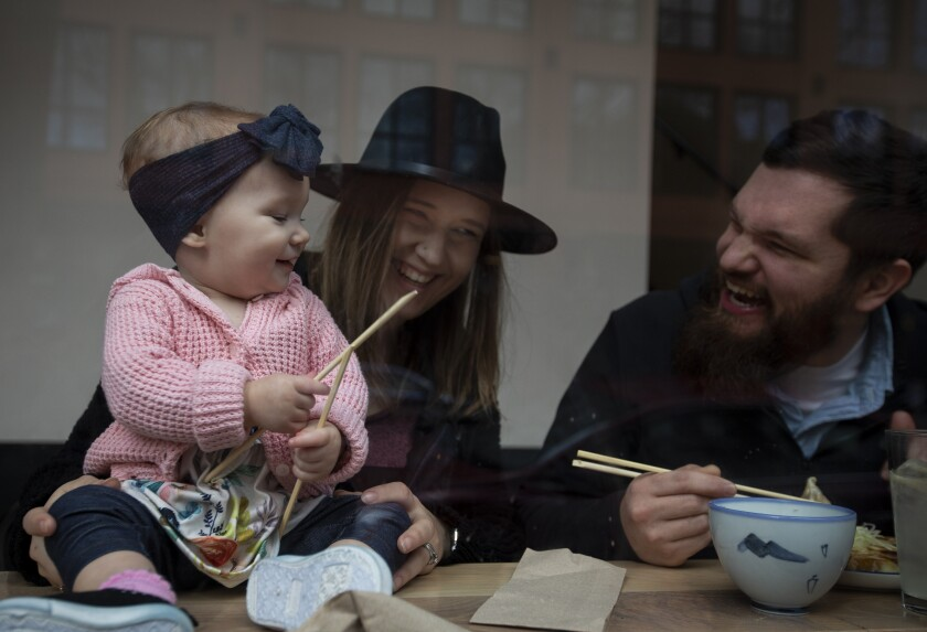 Everlyn Jorgenson, left, gets smiles from her parents, Emilie and Keaton Jorgenson, as they eat lunch at Afuri Ramen + Dumpling in Portland, Ore.