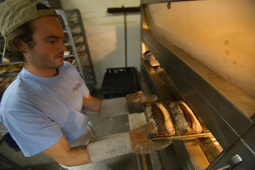 Louie Prager pulls from the oven freshly baked spelt loaves of bread. Louie Prager along with his brother Clinton Prager own and operate Prager Brothers Artisan Breads in Carlsbad.