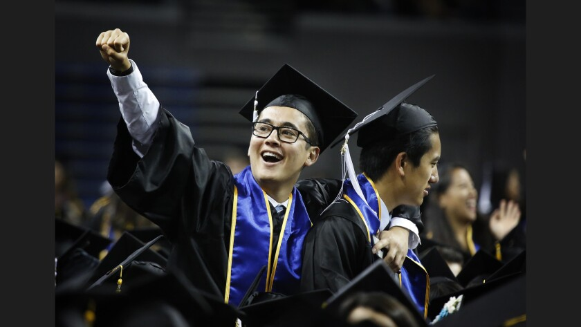 A UCLA student celebrates with a classmate during a graduation ceremony.