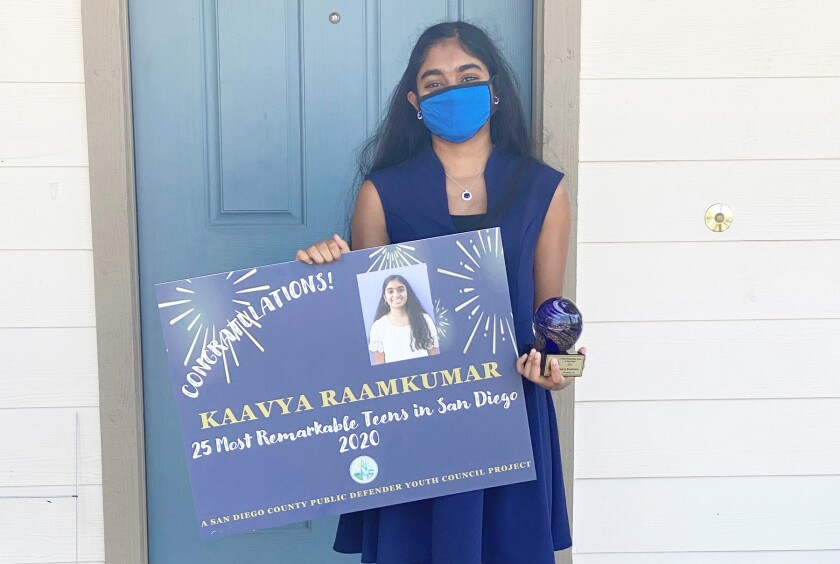 Kaavya Raamkumar holding her trophy and personalized yard sign at her 4S Ranch home last week.