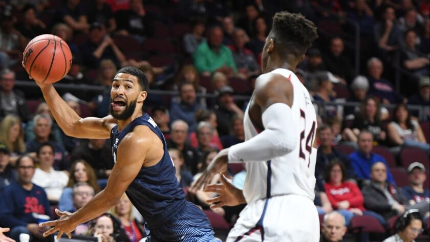 USD's Isaiah Wright (left) passes the ball as Saint Mary's Malik Fitts approaches during a WCC tournament semifinal game at the Orleans Arena in Las Vegas on March 11.