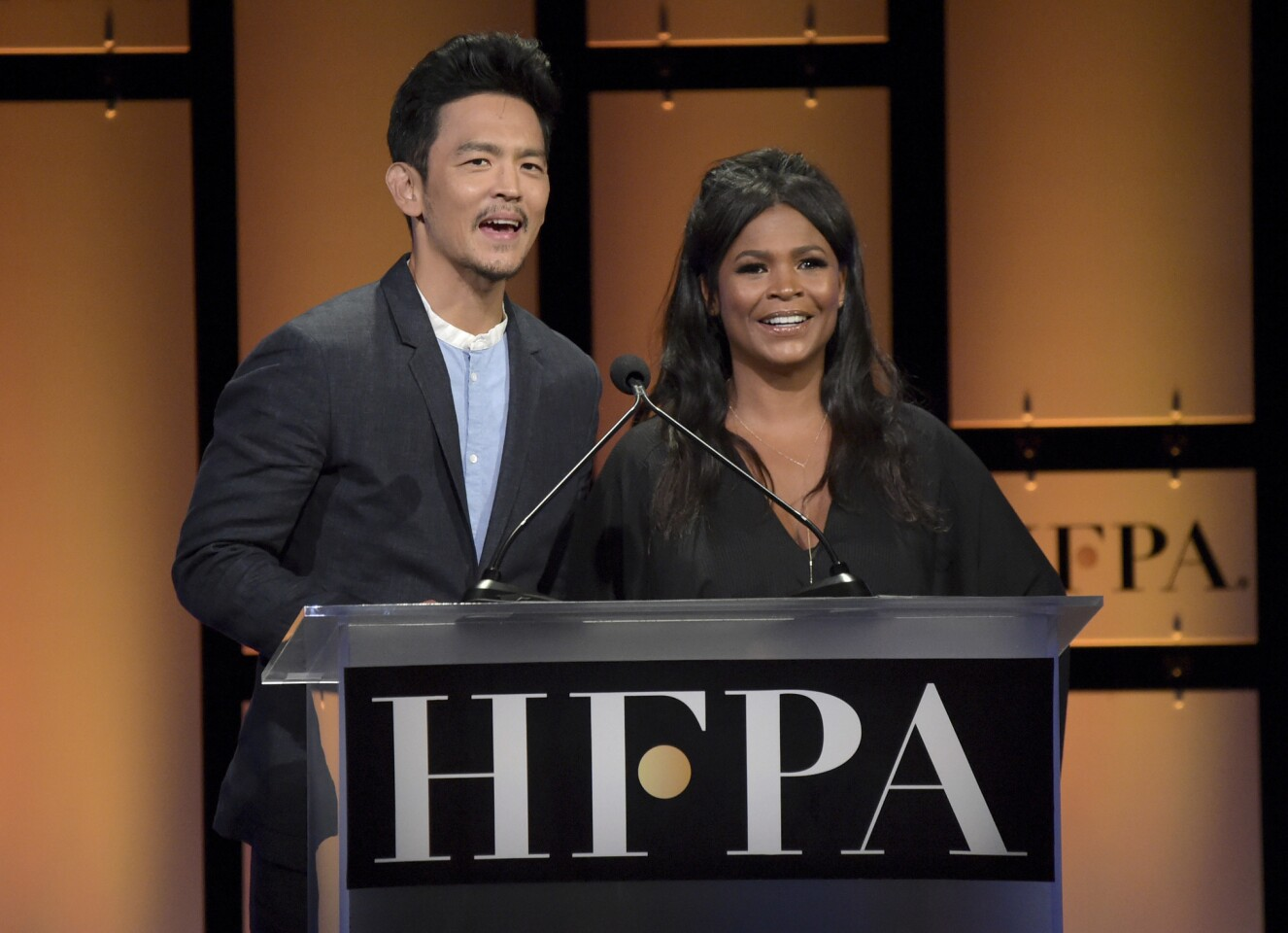 John Cho, left, and Nia Long speak at the Hollywood Foreign Press Association Grants Banquet at The Beverly Hilton hotel on Thursday, Aug. 9, 2018, in Beverly Hills, Calif.