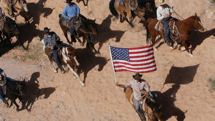FILE - In this April 12, 2014, file photo, the Bundy family and their supporters fly the American fl