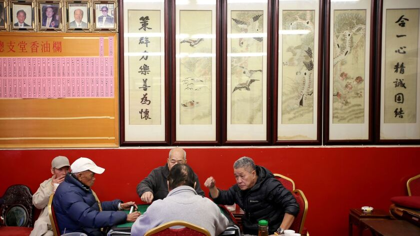 A group of men play mah-jongg at the Hop Sing Tong Benevolent Assn., a day after two men were fatally stabbed at the Chinatown club.