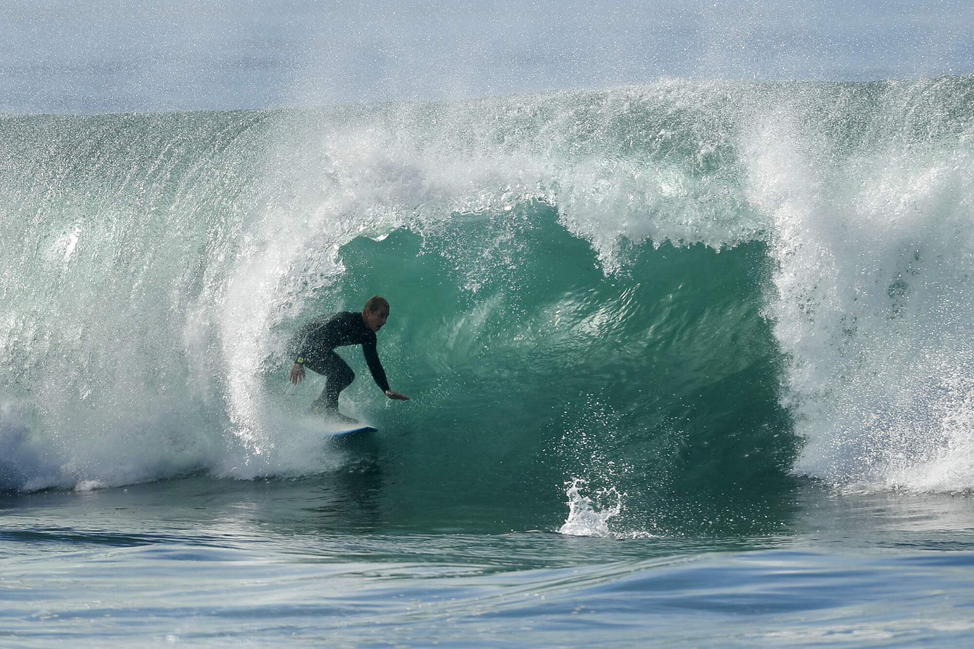 A surfer rides a wave in La Jolla on a warm, winter day on Sunday.