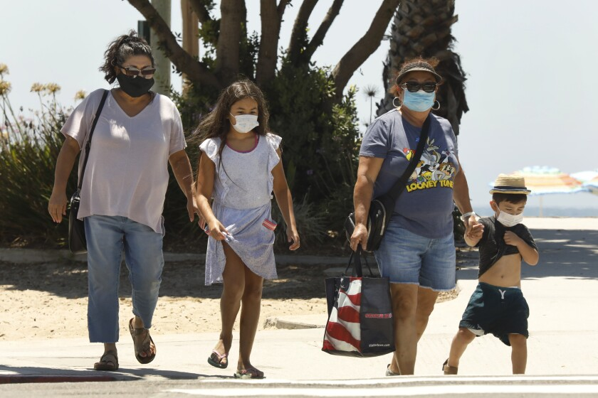 The Los Angeles-based Sanchez family wears their masks when they visit Laguna Beach on Friday, July 31, 2020. In Laguna Beach.