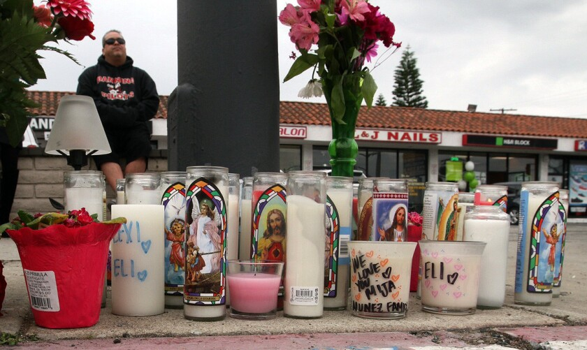 Gilberto Huerta sits at memorial to a brother and sister killed in a two-vehicle crash at 350 W. Pacific Coast Highway, near Island Avenue in Wilmington.