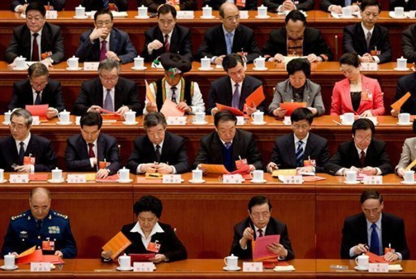FILE - In this March 14, 2013 file photo, delegates check the empty ballots before voting during a plenary session of the National People's Congress held at the Great Hall of the People in Beijing. Each was handed a ballot with one name on it: Xi Jinping. Each dropped it in a box. No mark was required to vote for Xi, so calling it rubberstamping suggests more work than there actually was. Any suspense about the choice of the Communist Party leadership was lifted in November, when Xi became the r