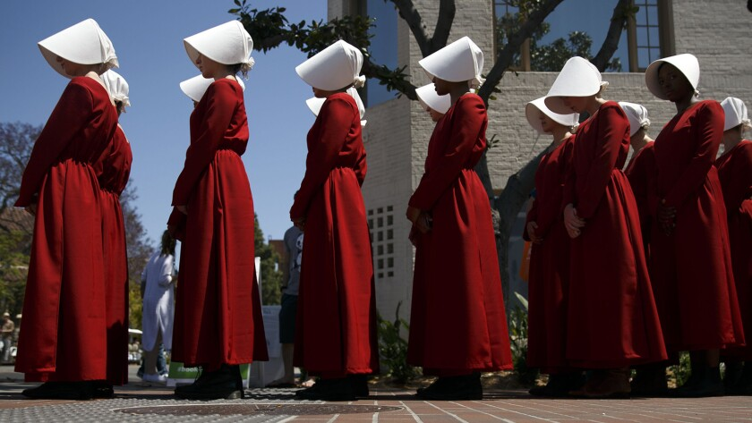 "Actresses from the Hulu series ""The Handmaid's Tale,"" based on the book by Margaret Atwood, stand in a row during the Los Angeles Times Festival of Books at the USC campus."