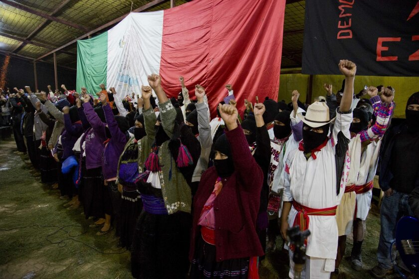 Masked members of the Zapatista National Liberation Army, EZLN, raise their fists during an event marking the 20th anniversary of the Zapatista uprising in the town of Oventic, Chiapas, Mexico, late Tuesday, Dec. 31, 2013. The revolt led Mexico to amend its constitution in 2001 to enshrine Indian r
