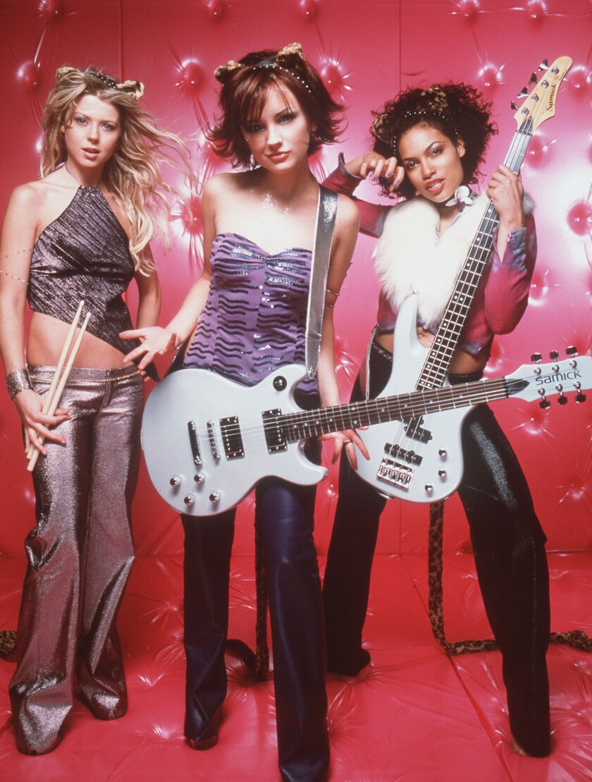 Three young women holding musical instruments.