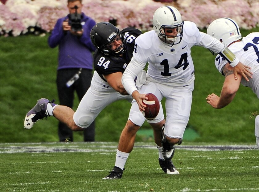 Penn State  quarterback Christian Hackenberg (14) is sacked by Northwestern defensive lineman Dean Lowry (94) during the first quarter of an NCAA college football game in Evanston, Ill.,  Saturday, Nov. 7, 2015. (AP Photo/Matt Marton)