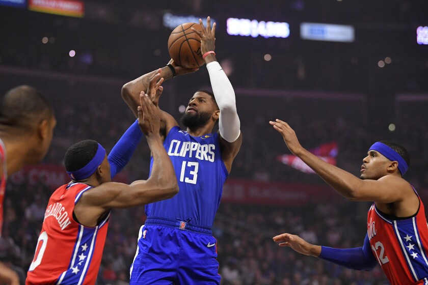 Clippers guard Paul George, center, shoots over Philadelphia 76ers guard Josh Richardson, left, and forward Tobias Harris during the Clippers' win Sunday.