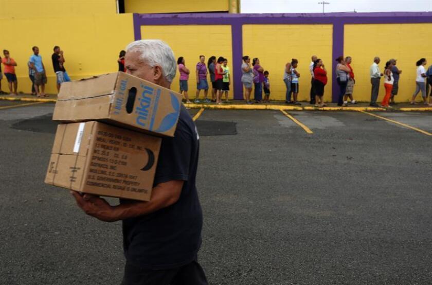 Un hombre camina con dos cajas de alimentos frente a una fila de personas damnificadas por el paso del huracán María. EFE/Archivo