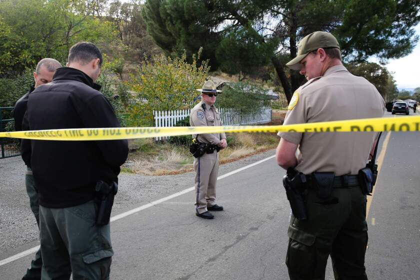 Law enforcement officers investigate at one of several crime scenes after a shooting rampage in Rancho Tehama, Calif.