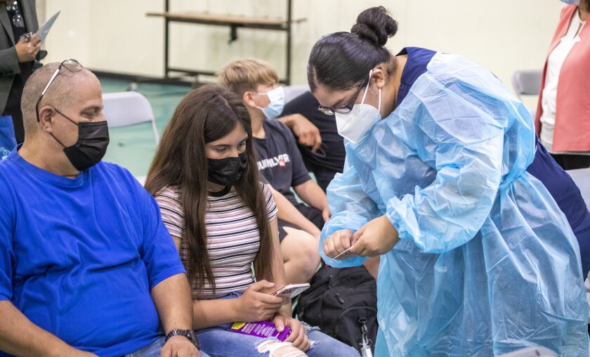 A woman in protective gear speaks with a girl and a man, seated in folding chairs and wearing masks.