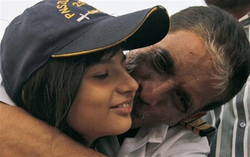 Pakistani Wasee Ahmed, right, the captain of the ship which was held captive by Somali pirates for nearly a year, kisses his daughter Laila, 11, in Karachi, Pakistan, Thursday, June 23, 2011. A group of 22 South Asian and Egyptian men held captive by Somali pirates for nearly a year received an emotional welcome in this southern port city Thursday after payment of a $2.1 million ransom secured their release. (AP Photo/Shakil Adil)